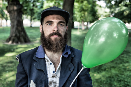 joblessness: Bearded vagrant with ballon close up