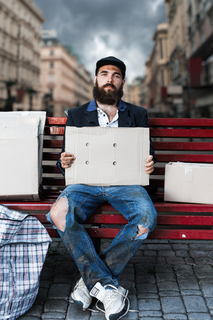 joblessness: Vagrant sitting with pieces of cardboard on the bench Stock Photo