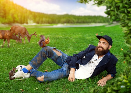 joblessness: Happy vagrant lying on the lawn with animals