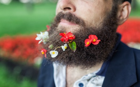 joblessness: Close up portrait of homeless with flowers in his beard