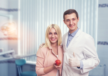 Happy woman stands with a dentist and holds an apple