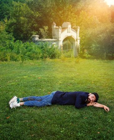 indigence: Homeless man sleeping on the green lawn Stock Photo