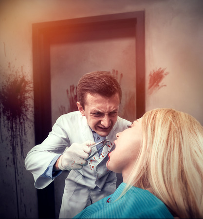 extracting: Mad scary dentist extracting a tooth in woman in dirty room