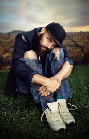 poorness: Sad vagrant sitting on the meadow