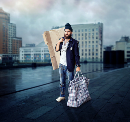 vagrant: Vagrant with a big bag in the street Stock Photo