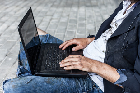 vagrant: Vagrant using laptop near the wall outdoor Stock Photo