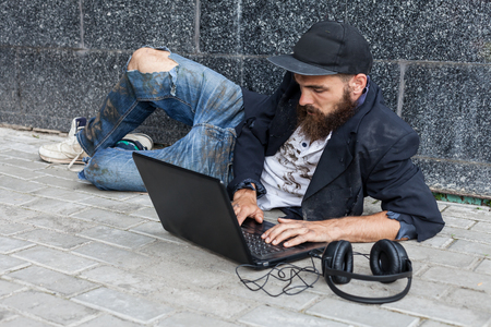 vagrant: Vagrant using laptop lying near the wall outside
