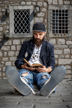 transient: Vagrant reading sitting on the street Stock Photo