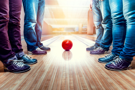 Many people standing near bowling ball on the lane