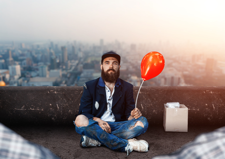joblessness: Vagrant with ballon sitting on the roof Stock Photo