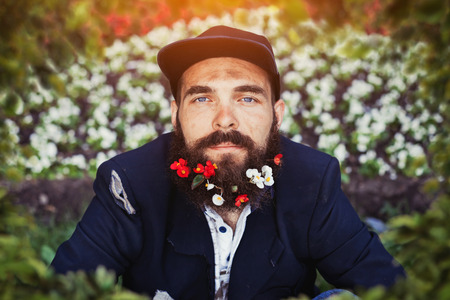 joblessness: Bearded homeless sitting in flowerbed with flowers in his beard Stock Photo