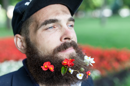 vagrant: Close up portrait of vagrant with flowers in his beard Stock Photo