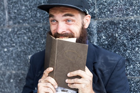 vagrant: Close up portraiit of excited vagrant biting book pages Stock Photo