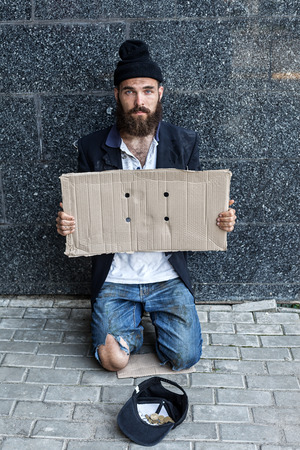 Begar with piece of cardboard on the street Stock Photo