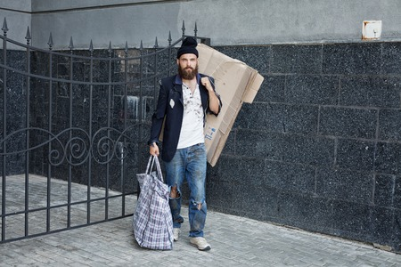 vagrant: Vagrant with a big bag is walking on the street Stock Photo