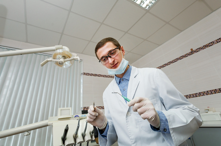 facemask: Professional male dentist holding instruments Stock Photo