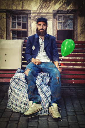 vagrant: Bearded vagrant with balloon sitting on the bench Stock Photo