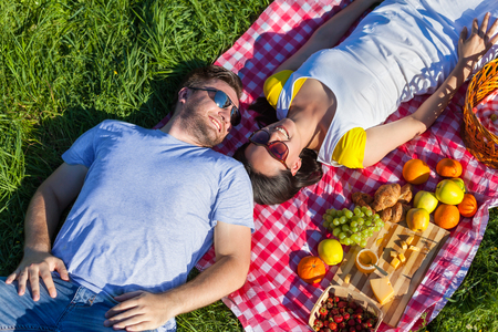 grass and sky: Young couple lying on the blanket during picnic