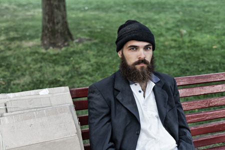 vagrant: Bearded vagrant sitting on the bench