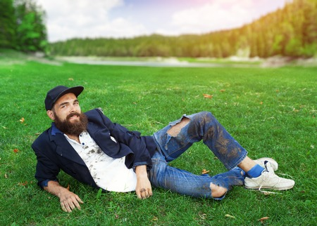 joblessness: Happy homeless lying on the lawn Stock Photo