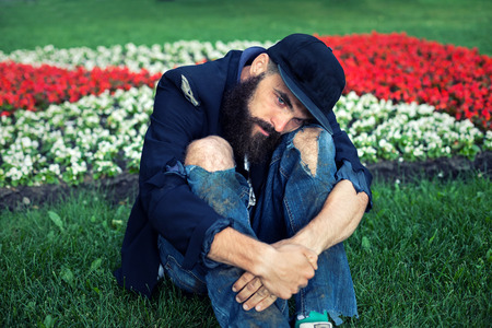 indigence: Sad vagrant sitting in flowerbed Stock Photo