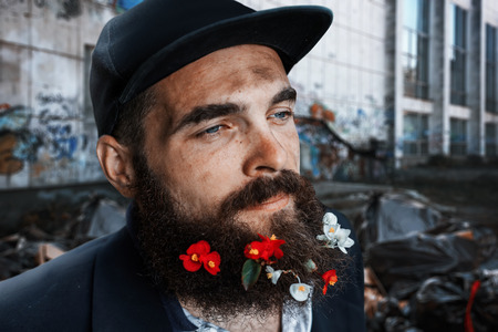 vagabond: Bearded homeless sitting in flowerbed with flowers in his beard Stock Photo
