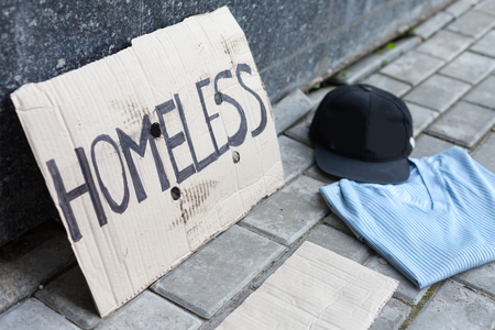 boite carton: Carton pour sans-abri, chemise et chapeau près du mur dans la ville