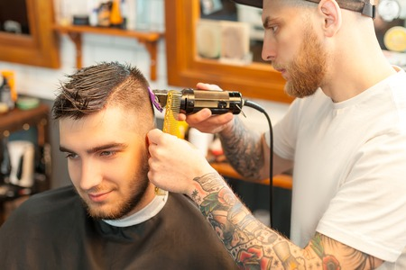 shorten: Side view of a young man having hair dress, barber working with hair clipper