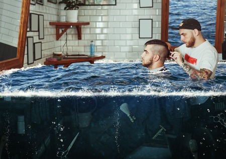 shorten: Young man having hair dress in flooded barbershop, barber working with hair clipper Stock Photo