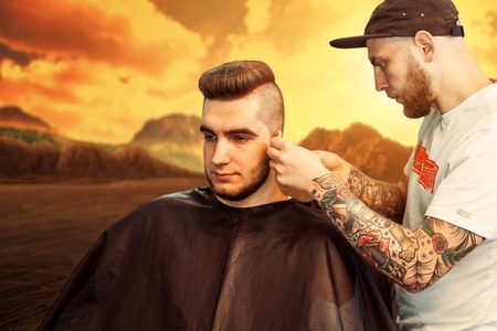 shorten: Young man having his beard shaven, barber working with trimmer in the desert Stock Photo