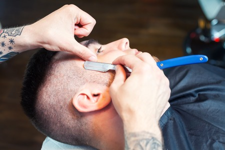 shorten: Young man having his beard shaven, barber working with razor in the salon Stock Photo