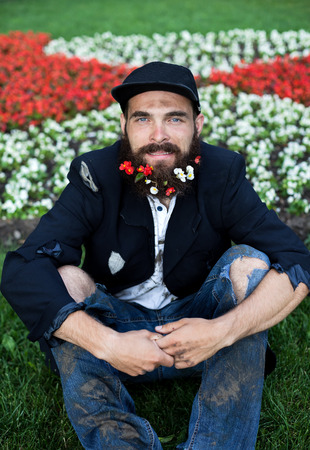 joblessness: Bearded vagrant sitting in flowerbed with flowers in his beard