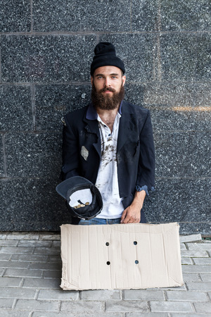 joblessness: Begar with piece of cardboard and a hat on the street Stock Photo