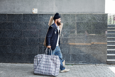 poorness: Vagrant with a big bag is walking along the building