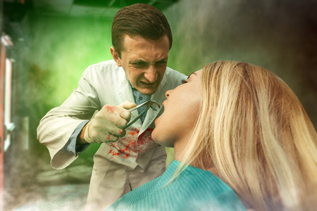 Mad bloodstained dentist extracting a tooth in woman, strange smoke is in the air Stock Photo