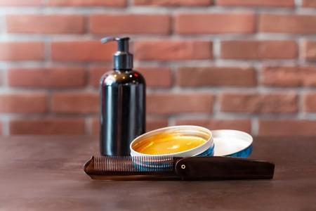 hair gel: Hair gel and hairbrush on the table over brick wall