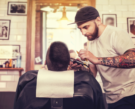 shorten: Young man having his beard shaven, barber working with trimmer in the salon