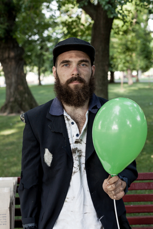 vagrant: Bearded vagrant with ballon in the park Stock Photo