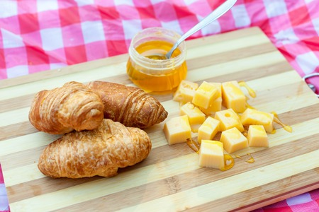 Croissants with cheese and honey on the board Stock Photo