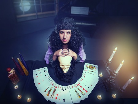 witchcraft: Sorceress practises witchcraft with pack of cards leaning on the skull Stock Photo