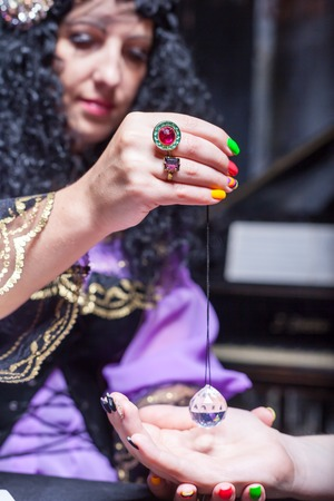astrologist: Sorceress reading somebodys hand using magic crystal
