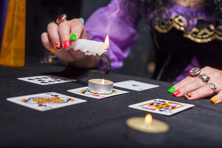 esoterism: Sorceress telling fortunes using cards and candles