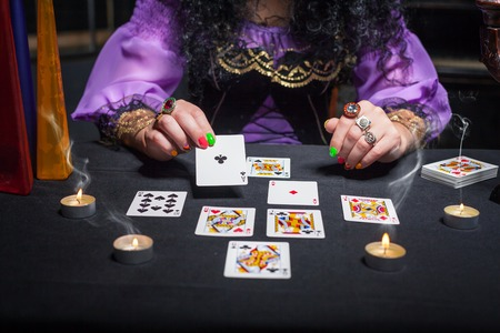 telepathy cards: Close up of sorceress telling fortunes using cards and candles