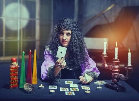 telepathy cards: Sorceress telling fortunes using cards, she shows holeinone Stock Photo