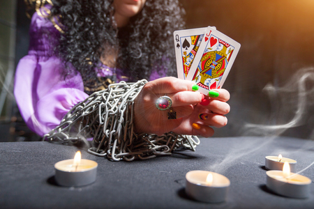 Sorceress with her hands loaded with chains telling fortunes using cards Stock Photo