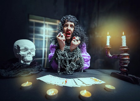 esoterism: Sorceress with her hands loaded with chains telling fortunes using cards Stock Photo