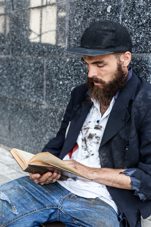 transient: Homeless is reading sitting outdoor