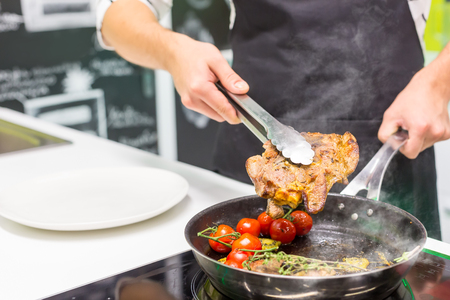Close up of chef cooking meat with vegetables Imagens