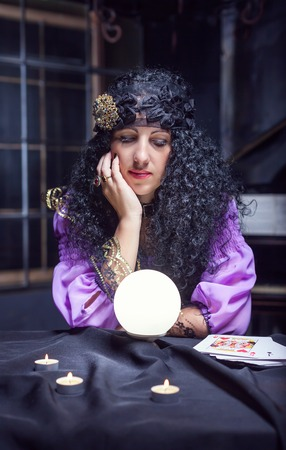 satanism: Sorceress looking at crystal ball in her room Stock Photo