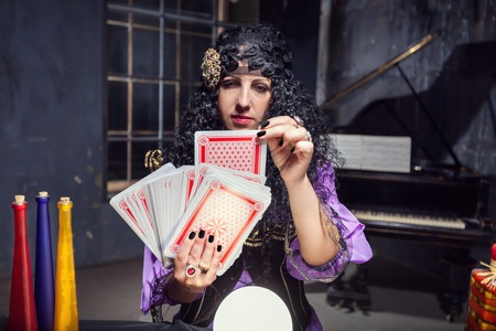 witchcraft: Sorceress practising witchcraft with cards in her room Stock Photo